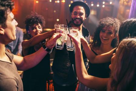 夜のクラブ パーティーで飲み物を持つ友人のグループです。若い人のバーで楽しむカクテルで乾杯します。 写真素材 - 71968052
