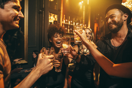 Schot van jonge mannen en vrouwen die van een feestje. Groep vrienden met drankjes bij nachtclub.