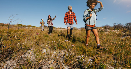 Group of friends on country walk on a summer day. Young people hiking in countryside. Stock Photo