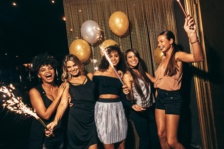 friends party: Group of women with fireworks at party. Stylish girls enjoying party at nightclub.