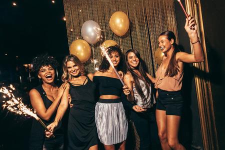 Groupe de femmes avec feux d'artifice en fête. Les filles élégantes apprécient la fête dans la boîte de nuit.
