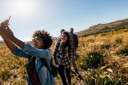 Gelukkige jonge vrouw nemen van foto's van vrienden tijdens het wandelen. Groep vrienden op landgang nemen selfie.