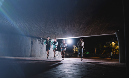 Group of runners running under a bridge in city. Young men and women jogging together at night.
