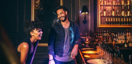 Pareja feliz en el mostrador de bar discoteca y la risa. Los jóvenes se divierten en un club.