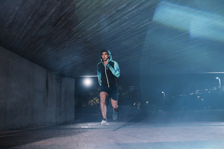 Healthy young man jogging in the city at night. Full length shot of male athlete running under bridge. 版權商用圖片