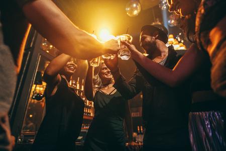 Lage hoek schot van groep vrienden genieten van een drankje bij de bar bij elkaar. Jonge mensen bij nachtclub roosteren cocktails. Stockfoto