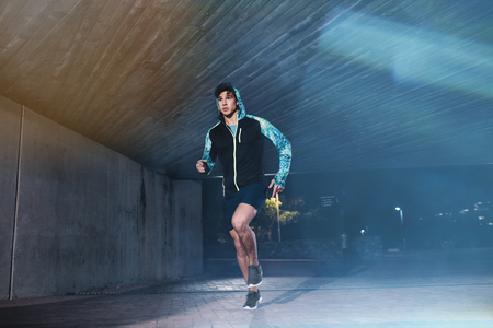 full shot: Full length shot of young athlete running under bridge in city. Fit young man jogging in the city. Stock Photo
