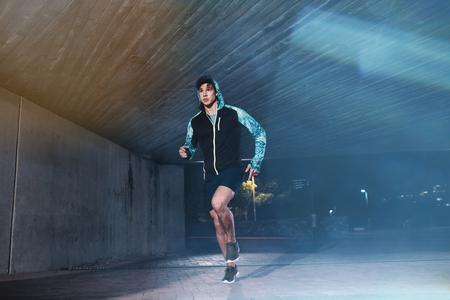 Volledige lengte shot van jonge atleet die onder de brug in de stad. Fit jonge man joggen in de stad.