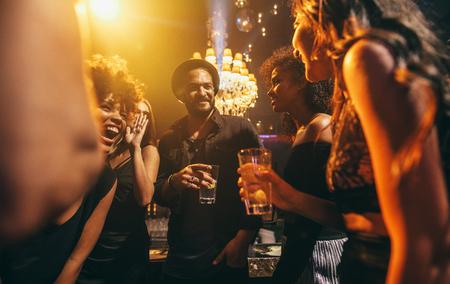 イメージのパブでパーティを楽しんでいる友人のグループ。ナイトクラブで楽しんで幸せな若者。 写真素材