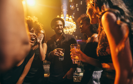 Image group of friends enjoying a party at pub. Happy young people having fun at nightclub. Stock Photo