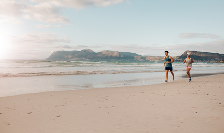 sportsperson: Shot of young couple running together on the sea coast in morning. Morning run on the beach