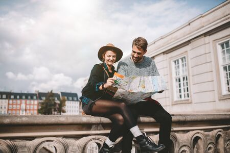 find: Young tourist couple exploring the navigation map of a city. Happy couple sitting on bridge on a cloudy day looking at a map.