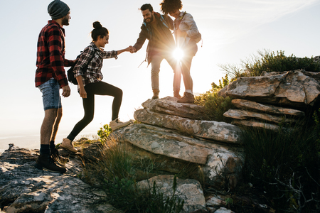Group of friends hiking in mountain. Four hikers walking on a mountain at sunset. Фото со стока