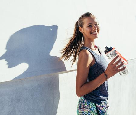 Shot van mooie vrouwelijke agent staande buiten bedrijf fles water. Fitness vrouw die een pauze na het uitvoeren van training.