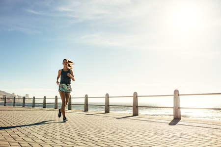 Full length shot of healthy young woman running on the sea side promenade. Female runner working out on a sunny morning.