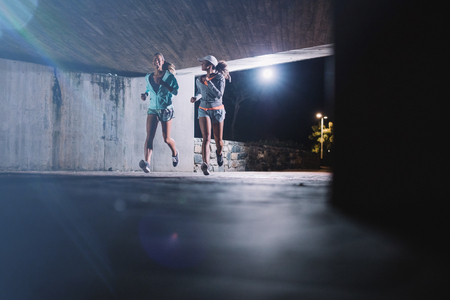 Two young women jogging at night in city. Female runners working out together under a bridge in evening. 版權商用圖片