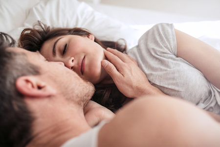 parejas enamoradas: Young woman lying on bed with man. Romantic young couple on bed.