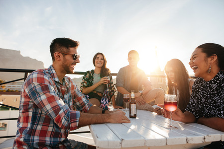 옥상에서 칵테일 파티를 친구의 다민족 그룹. 젊은 남자와 여자 음료 테이블 주위에 앉아 웃고.