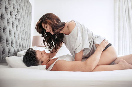 Sensual young couple looking at each other passionately on bed in morning.