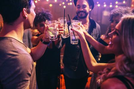Groep jonge vrienden in club roosteren met cocktails. Jonge mannen en vrouwen die bij nachtclub vieren met een drankje.