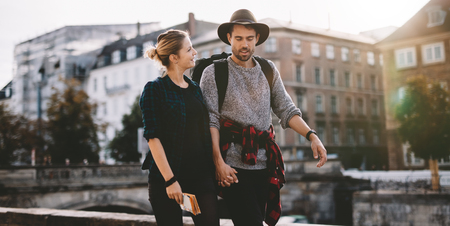 holding hands while walking: Smiling young couple walking on street holding hands. Young man wearing hat while the woman is holding a map. Stock Photo
