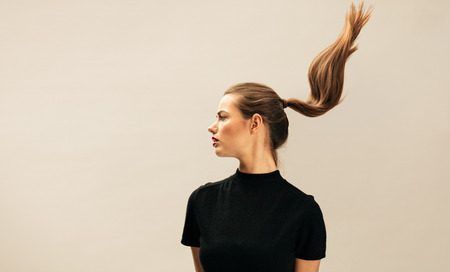 Side view of pretty young woman with long hair. Fashion model looking away over beige background. 스톡 콘텐츠