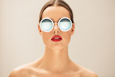 Nahaufnahme Porträt der hübschen jungen Frau mit Brille gegen beige Hintergrund. Weibliche Mode-Modell posiert mit Sonnenbrille.