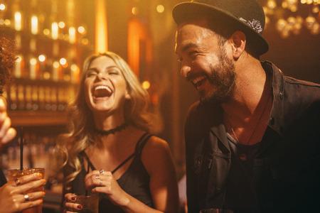 Grupa ludzi bawiących się w pubie. Młodzi przyjaciele spędzają noc w klubie.
