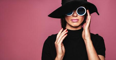 Cerca de retrato de modelo de mujer caucásica con estilo. Mujer en el sombrero y gafas de sol que presenta sobre el fondo de color rosa.