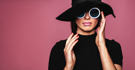 Close up portrait of stylish caucasian female model. Woman in hat and sunglasses posing over pink background. Foto de archivo