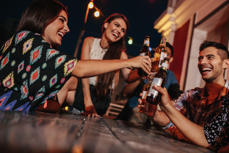 Group of friends toasting drinks at a party in evening. Young people hanging out at rooftop party and enjoying drinks.