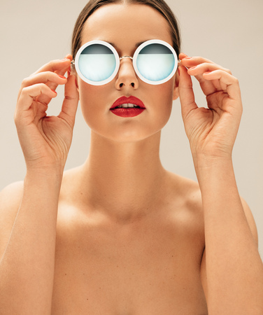 1: Close up portrait of shirtless female model wearing sunglasses. Beautiful young woman posing with glasses. Stock Photo