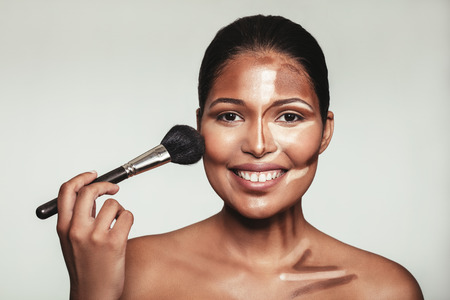 Close up portrait of contour and highlight makeup on female model. Woman applying makeup on her face with brush.