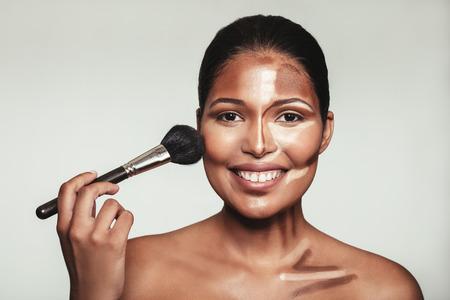 Close-up portret van contour en highlight make-up op vrouwelijk model. Vrouw aanbrengen make-up op haar gezicht met penseel. Stockfoto