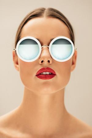サングラスを身に着けている若い女性の垂直肖像画を間近します。白人女性のモデルはベージュの背景にポーズします。