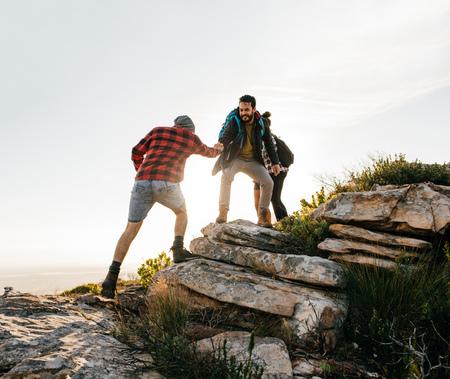 Gruppo di escursionisti a piedi nella natura. Amici che fanno un'escursione su una montagna. Archivio Fotografico - 74295977