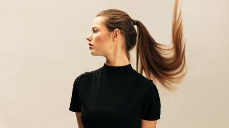 Ritratto laterale di bella giovane bruna su sfondo beige. Modello femminile di moda con i capelli lunghi.