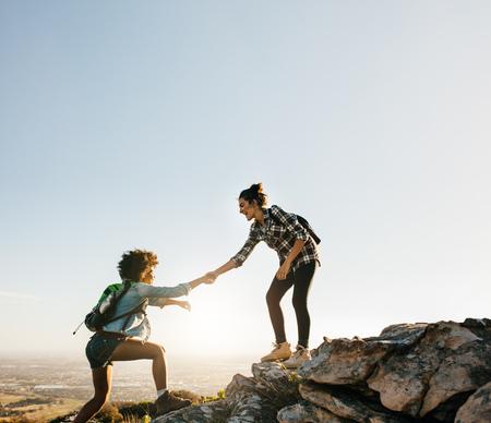 mujeres: Las amigas caminando se ayudan mutuamente en las montañas. Caminante femenino joven que ayuda a amigo mientras que trekking en montaña. Foto de archivo