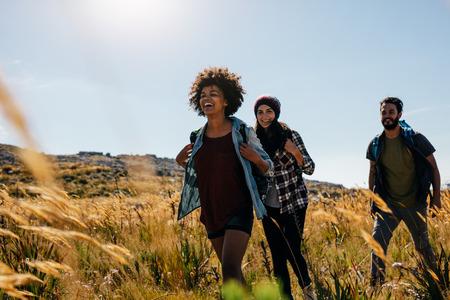 一緒に田舎を散策の友達のグループ。幸せな若い男性と女性の夏の日に一緒にハイキングします。