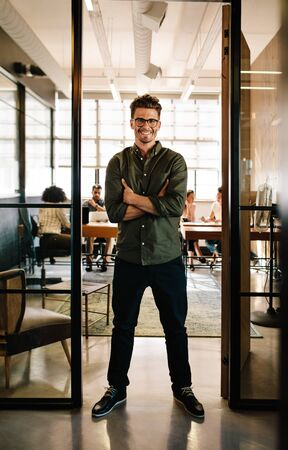 Full length portrait of smiling young man standing in doorway of office with his arms crossed. Creative male executive at startup with people working in background.