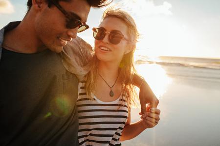 夏の日にビーチで彼氏と美しい女性のショット。夏の休日にカップルを愛する。