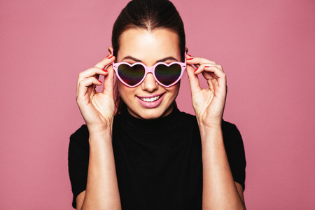 Portrait of stylish young woman with heart shaped sunglasses over pink background. Caucasian fashion model posing with funky shades.