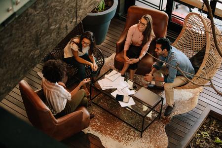 사무실 로비에 앉아 새로운 아이디어를 논의하는 4 명의 비즈니스 동료의 상위 뷰. 사무실에서 기업 비즈니스 팀 회의입니다.