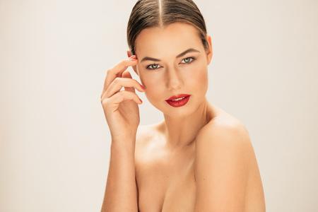 Portret van jonge natuurlijke schoonheid met een mooie huid te kijken naar de camera. Vrouwelijk model met verse schone en heldere huid tegen beige achtergrond.