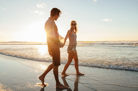 Outdoor shot of romantic young couple walking along the sea shore. Young man and woman walking on the beach together at sunset.