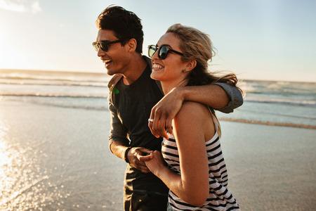 해변에 산책하는 젊은 부부 미소의 야외 쐈 어. 젊은 남자와 여자의 여름날에 해변에 함께 산책.