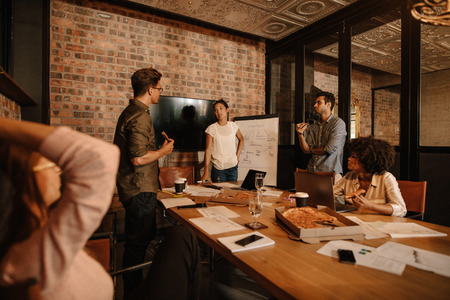 Shot of a group of young business professionals having a meeting in boardroom. Office workers discussing new business strategy together in a conference room.