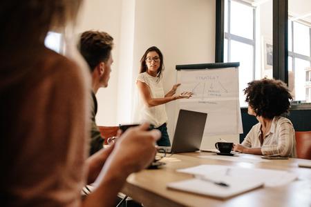 Kobieta wykonawczy wyjaśniając nową strategię biznesową dla kolegów w sali konferencyjnej. Spotkanie zespołu zespołu w biurze.