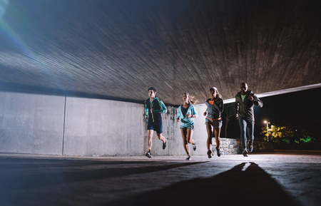 Group of young men and women running together at night. Healthy young people training together under a bridge in city. Stock Photo