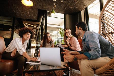 Zespół biznesowych siedzi w holu pakietu office i sesji burzy mózgów. Happy przedsi? Biorców posiedzenia wraz z laptopem i dyskusji. Zdjęcie Seryjne